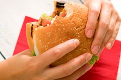 Close up photo of eating hamburger. Woman holding home made hamburger and biting Stock Image