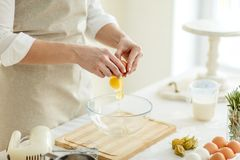 Close up photo. eggs yolk is dropping in the plate. Girl is making a dough for pancakes royalty free stock photography