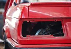 Close-up photo of empty backlight slot car. Close-up photo backlight of red rusty car Royalty Free Stock Photo
