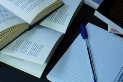 Books, Note book and pen. Close up photo of an empty note book with a blue pen on top a d a bunch of poetry books stock images