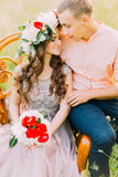 Close-up photo of fashionable cool couple sitting embracing on wooden vintage chair in the garden Stock Photos