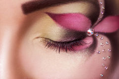 Close up photo of female closed eye with flower make up. In studio Stock Image