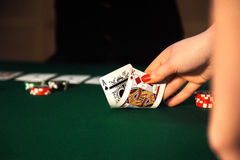Close-up photo of female hand that raises cards from the table. In the casino Stock Photography