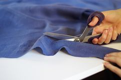 Close up photo of female hand with the scissors cutting the violet fabric. Tailoring Process Stock Photo