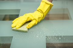 Close-up photo of female hand washing glass table in with cleaning spray and sponge wearing gloves in apartment.  Stock Image