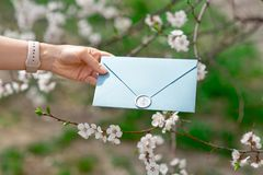 Close-up photo of female hands holding a blue invitation envelope with a wax seal, a gift certificate, a postcard, a. Wedding invitation card on the background stock photo