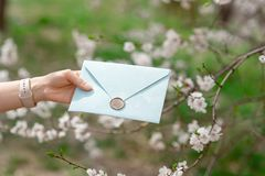 Close-up photo of female hands holding a blue invitation envelope with a wax seal, a gift certificate, a postcard, a stock photo