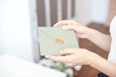 Close-up photo of female hands holding a silver blue or pink invitation envelope with a wax seal, a gift certificate, a. Postcard, a wedding invitation card royalty free stock photography