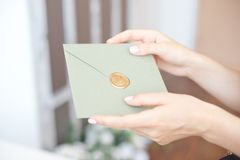 Close-up photo of female hands holding a silver blue or pink invitation envelope with a wax seal, a gift certificate, a. Postcard, a wedding invitation card royalty free stock images