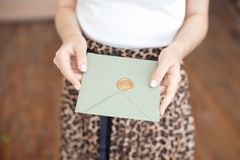 Close-up photo of female hands holding a silver blue or pink invitation envelope with a wax seal, a gift certificate, a. Postcard, a wedding invitation card stock images