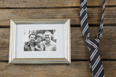 Close up of photo frame with necktie. On wooden table Royalty Free Stock Image