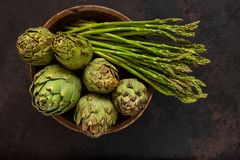 Close up photo of fresh artichoke in the old wooden bowl and Bunch of green asparagus. Top view on dark background stock photography