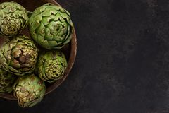 Close up photo of fresh artichoke in the old wooden bowl. Top view on dark background royalty free stock image