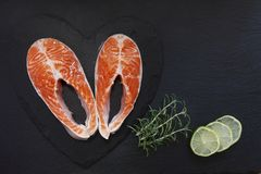 Close-up photo of fresh salmon fish with sea salt and lime slices on black table background. stock photo