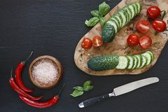 Close-up photo of fresh vegetables on wooden cutting board with knife on black concreted table background. Top view Stock Images