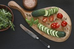 Close-up photo of fresh vegetables on wooden cutting board with knife on black concreted table background. Top view Stock Image
