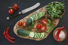 Close-up photo of fresh vegetables on wooden cutting board with knife on black concreted table background. Top view Royalty Free Stock Image