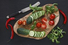 Close-up photo of fresh vegetables on wooden cutting board with knife on black concreted table background. Top view Royalty Free Stock Photo