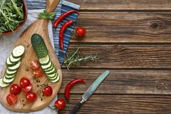 Close-up photo of fresh vegetables on wooden cutting board with knife on vintage wooden background. Top wiew Stock Images