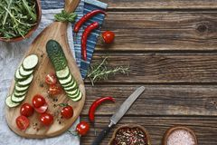 Close-up photo of fresh vegetables on wooden cutting board with knife on vintage wooden background. Top view Stock Images