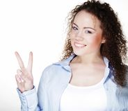 Close-up photo of funny young woman showing OK gesture, looking at camera royalty free stock image