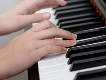 Close up photo of girls hands playing on piano Royalty Free Stock Photos