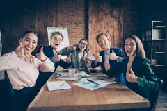 Close up photo glad she her he him his all dressed in formal wear jackets and shirts holding hands like alright symbol. Smiling accepting employee team sitting stock photo
