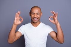 Close up photo glad toothy dark skin he him his macho bald head approve show okey advise agree alright hundred per sent. Wearing white t-shirt outfit clothes stock photography