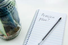 A close up photo of a glass jar full of South African money, a pen and notepad with a plain background. This image represents the concept of drawing up a Royalty Free Stock Photo