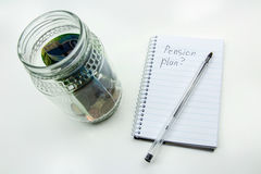 A close up photo of a glass jar full of South African money, a pen and notepad with a plain background. This image represents the concept of drawing up a Stock Images