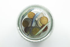 A close up photo of a glass jar full of South African money with a plain background stock photos
