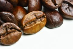 Close-up photo of grains of roasted black coffee on a white back Stock Photos