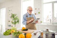 Close up photo grey haired he his him grandpa hands arms e-reader not interested in cooking watch read reader internet stock photography