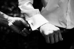 Close-up photo of groomsman helping to put cufflinks on groom. B. Lack and white photo stock images
