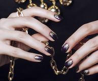 Close up photo hands with gold manicure holding chain on black Royalty Free Stock Photos