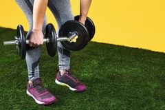 Close up photo of handsome fit young woman legs exercises with dumbbells on the green grass over yellow background. Close up photo of handsome fit young woman royalty free stock images