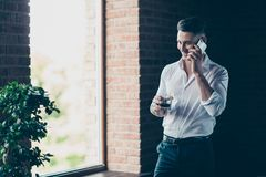 Close up photo handsome he him his hands arms whisky beverage enjoy telephone communication tell speak partners wear. Formal-wear dress code shirt pants stock images