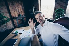 Close up photo handsome he him his macho guy cheer friendly look watch telephone make take selfies wave hand arm say hi. Hey hello notebook table stand office royalty free stock image