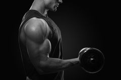 Close-up photo of handsome power athletic man in training pumping up muscles with dumbbell. Strong bodybuilder with perfect royalty free stock image