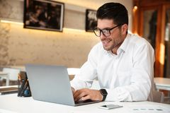 Close-up photo of handsome smiling businessman in white shirt us. Ing laptop in office Royalty Free Stock Photography