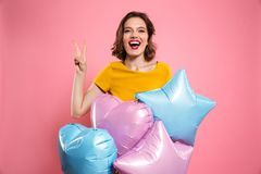 Close-up photo of happy birthday girl with red lips holding ball. Oons, showing peace gesture, looking at camera, isolated on pink background Stock Photography