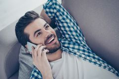 Close up photo of happy excited man in checkered shirt lying on. Sofa and talking on mobile phone Royalty Free Stock Images
