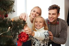 Happy family decorating christmas tree at home. Close-up photo of happy family decorating christmas tree at home stock image