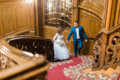 Close-up photo of the happy newlyweds holding hands while going up ancient stairs. Royalty Free Stock Photography
