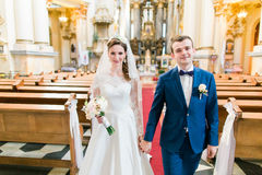 Close-up photo of happy stylish newlyweds walking holding hands in the church  on wedding ceremony Royalty Free Stock Photography