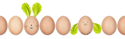 Close-up photo of hen's eggs with eggshell texture in a row. Funny Easter bunny and chicken made of eggs and salad leaves. stock photo