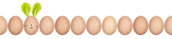 Close-up photo of hen's eggs with eggshell texture in a row. One egg has Easter bunny ears made of salad leaves and funny face stock images