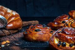 Close up photo of homemade buns and fresh cinnamon with cinnamon, almonds, star anise on dark rustik background. royalty free stock photography