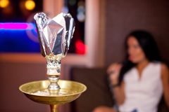Close-up photo of hookah with smoking girl on background.  Royalty Free Stock Images