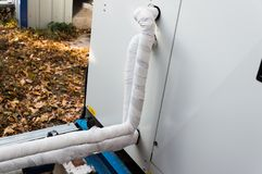Close-up view of the insulated refrigerant pipelines connected to the air handling unit. Close-up photo of the insulated refrigerant pipelines connected to the Stock Photography